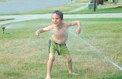 Het Spelen van de jongen in de Sproeier Stock Foto