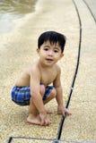 Het spelen van de jongen door de rand van het water stock afbeeldingen