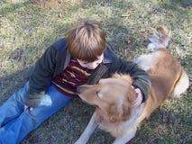Jongen en hond het spelen op gebied royalty-vrije stock foto