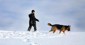 Het spelen van de jongen en van de hond in sneeuw Royalty-vrije Stock Foto