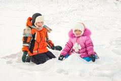 Het spelen van de jongen en van het meisje op de sneeuw stock afbeeldingen