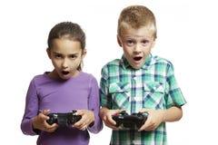 Het spelen van de jongen en van het meisje spelenconsole Stock Afbeeldingen