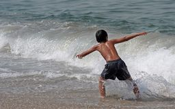 Het spelen van de jongen in het overzees Stock Foto