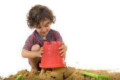 Het spelen van de jongen in het zand Stock Foto's
