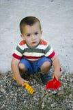 Het spelen van de jongen in kiezelstenen royalty-vrije stock fotografie