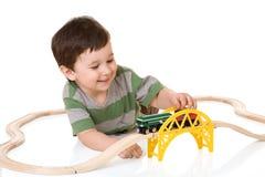 Het spelen van de jongen met een treinreeks Stock Fotografie