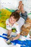 Het spelen van de jongen met het schilderen Stock Afbeelding