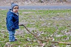 Het spelen van de jongen met lange stok Stock Afbeeldingen