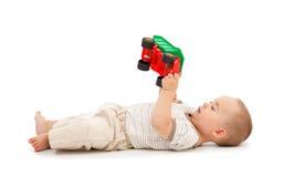 Het spelen van de jongen met plastic stuk speelgoed auto Stock Foto