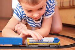 Het spelen van de jongen met stuk speelgoed spoorweg royalty-vrije stock afbeelding