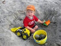 Het spelen van de jongen met vrachtwagens bij het strand Stock Fotografie