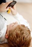 Het spelen van de jongen met zijn cellphone Stock Fotografie
