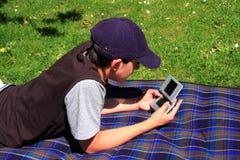 Het spelen van de jongen met zijn consolespel Stock Foto