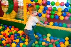 Het spelen van de jongen op de speelplaats Stock Afbeelding
