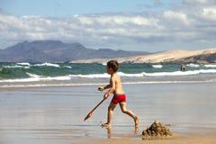 Het spelen van de jongen op het strand Stock Foto