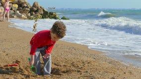 Het spelen van de jongen op het strand stock video