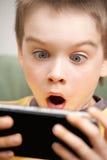 Het spelen van de jongen spelconsole Stock Afbeelding