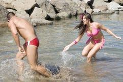 Het spelen van de man en van de vrouw met het water Stock Fotografie