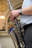 Het spelen van de mens saxofoon of messingshoorn (muzikaal instrument) Royalty-vrije Stock Foto