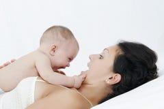 Het spelen van de moeder en van de dochter op wit bed Stock Fotografie