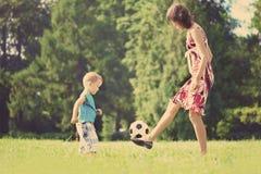Het spelen van de moeder en van de zoon bal in het park stock foto's