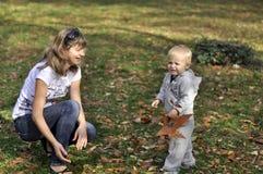 Het spelen van de moeder en van de zoon in het park in de herfst Stock Foto's