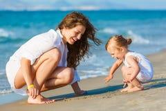 Het spelen van de moeder met dochter op het strand stock fotografie