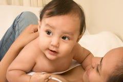 Het spelen van de moeder met haar zoon van de babyjongen op bed Royalty-vrije Stock Fotografie