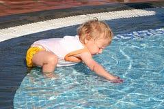 Het spelen van de peuter in pool Stock Foto's