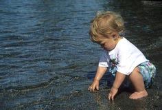 Het spelen van de peuter in water stock foto