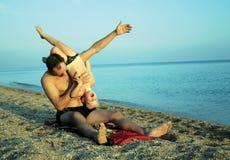 Het spelen van de vader en van de zoon op het strand Stock Foto