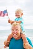 Het spelen van de vader en van de zoon op het strand Stock Foto's