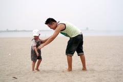 Het spelen van de vader en van de zoon op strand Stock Afbeeldingen