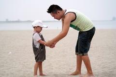 Het spelen van de vader en van de zoon op strand Stock Foto