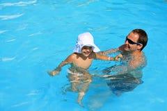 Het spelen van een vader en een dochter bij de pool Stock Foto's