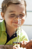 Het spelen van het jonge geitje met water Stock Fotografie