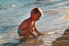 Het spelen van het jonge geitje op het strand Stock Foto's