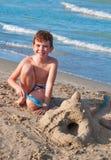 Het spelen van het jonge geitje op het strand Stock Fotografie