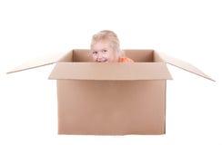 Het spelen van het kind in een doos Royalty-vrije Stock Afbeeldingen