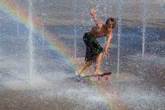 Het spelen van het kind in fontein met skateboard stock foto