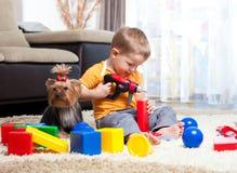 Het spelen van het kind met bouwstenen met hond binnen stock foto