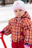 Het spelen van het kind met spade in sneeuw Stock Foto