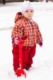 Het spelen van het kind met spade in sneeuw Stock Afbeelding