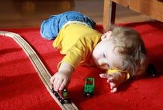 Het Spelen van het kind met Treinen thuis royalty-vrije stock afbeelding