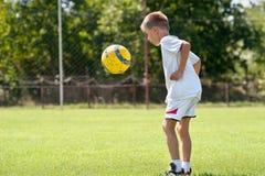 Het spelen van het kind voetbalbal stock afbeelding