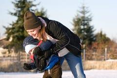 Het spelen van het mamma en van de zoon in sneeuw Stock Afbeeldingen