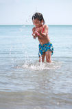 Het spelen van het meisje bij het strand stock afbeelding