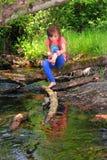 Het spelen van het meisje in een kreek stock foto