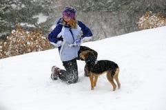 Het spelen van het meisje en van het puppy in sneeuw stock afbeelding
