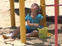 Het spelen van het meisje in het zand stock foto's